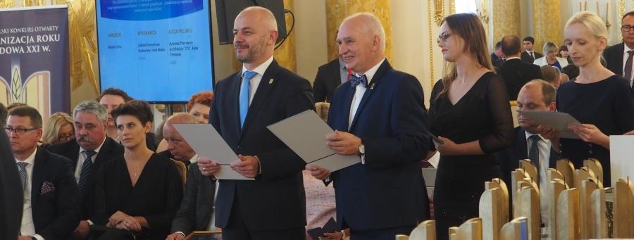 w stylowej sali stoją mężczyźni, którzy trzymają w rękach dyplomy. Obok na stole ustawione są złote statuetki. Wokół siedzą goście gali w oczekiwaniu na wręczenie nagród