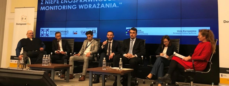 Sześcioro uczestników i prowadząca panel członkini jednego z zespołów monitorujących siedzą na podium. W środku z mikrofonem w ręku dyrektor Marcin Cudak. Z boku stoi tłumacz migowy wykonujący tłumaczenie.