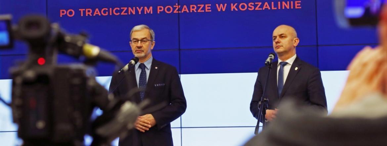 Minister Jerzy Kwieciński i GINB Norbert Książek na tle napisu Kontrole budowlane po tragicznym pożarze w Koszalinie